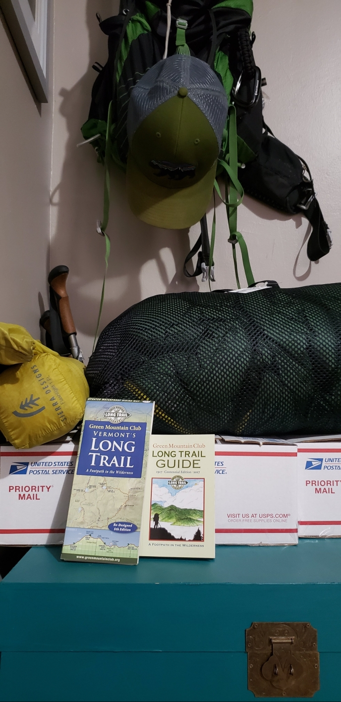 Hiking bag hangs in the background with a rolled up sleeping bag and tent on top of three white USPS flat rate boxes. In front of the boxes are a Long Trail guide and map.