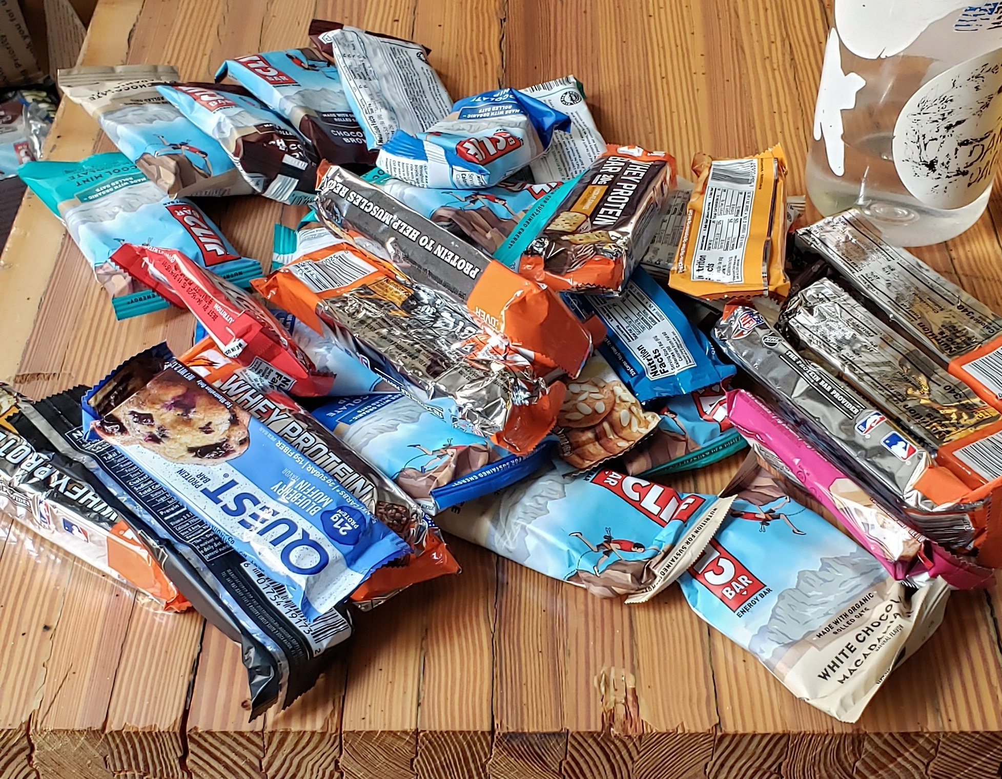 A big pile of various protein bars spread across a wooden table.