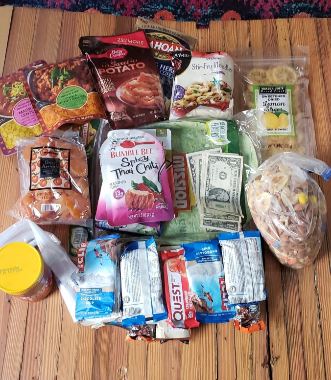 On a wooden table there is a full spread of hiking food including quick cooking meals, dried fruit, protein bars, tuna packets, wraps, and dollar bills