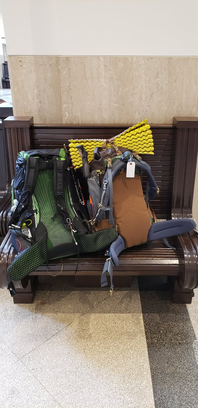 Two hiking backpacks fully loaded are taking up a wooden bus station bench.