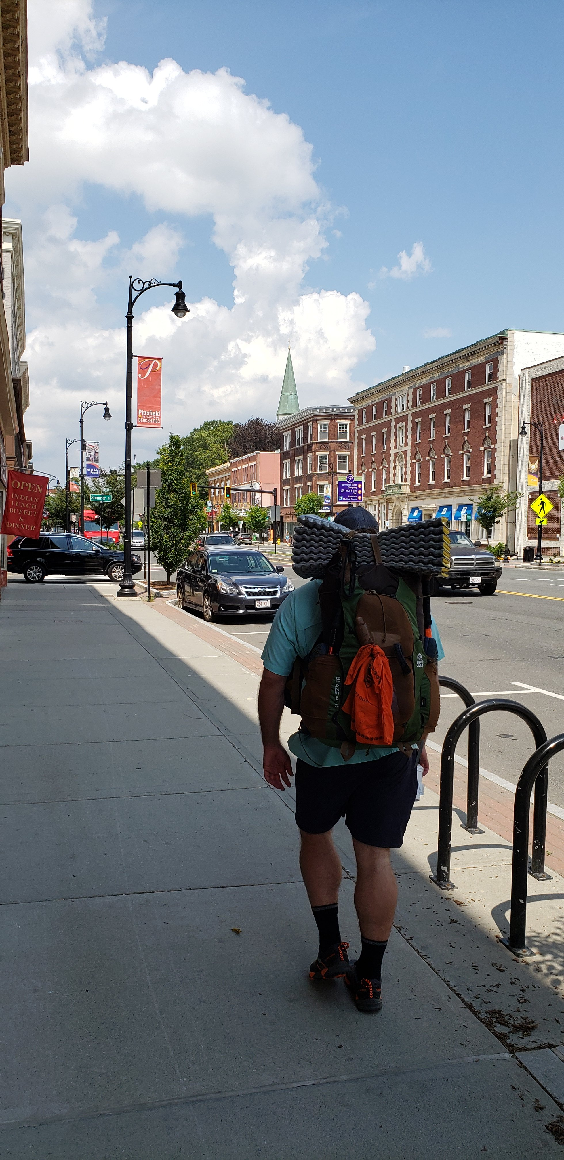 A hiker walks in the foreground of a brick building, small town downtown. The sky is blue and a church steeple can be seen in the background.