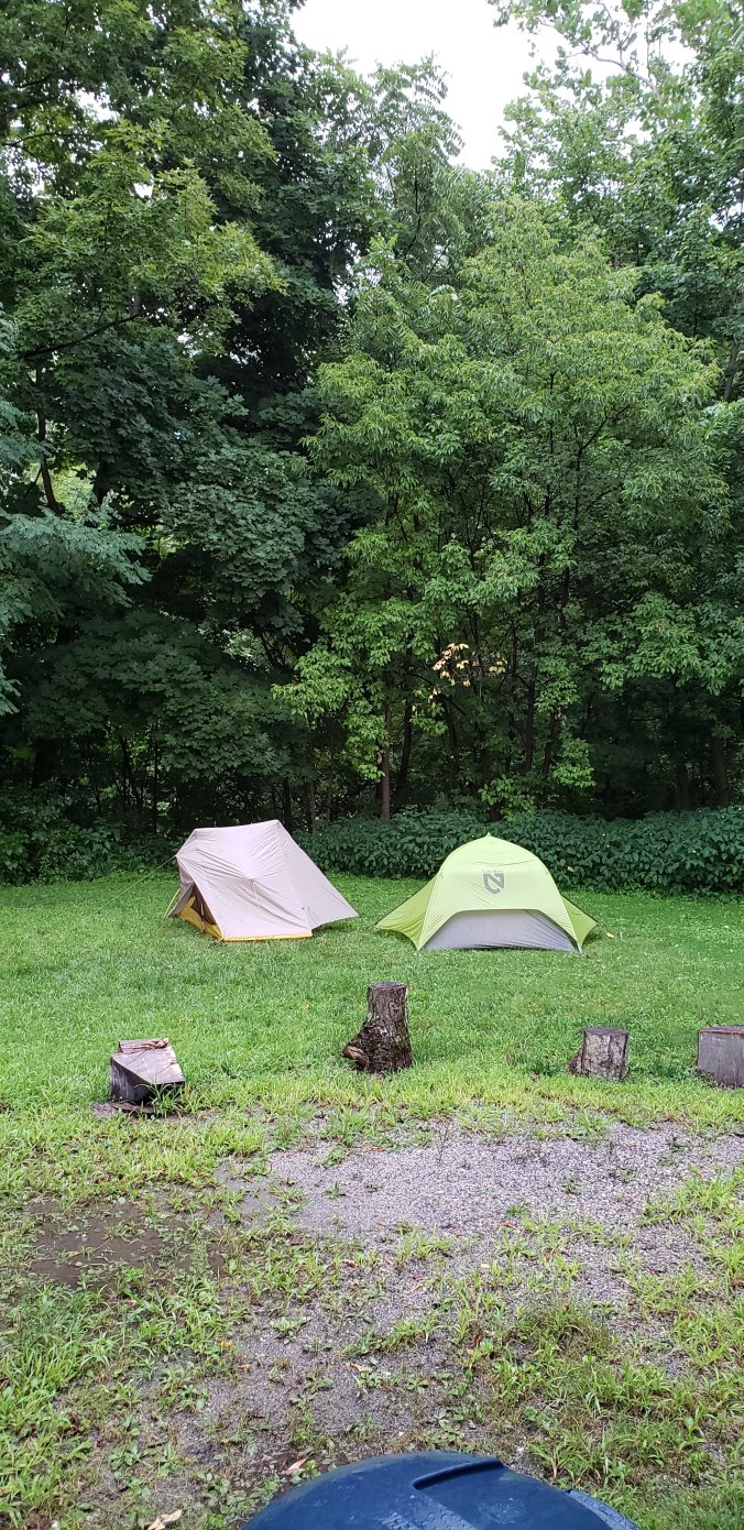Two tents, one yellow and gray the other bright green, on a level lawn. Trees can be seen in the background and the ground is wet with rain.