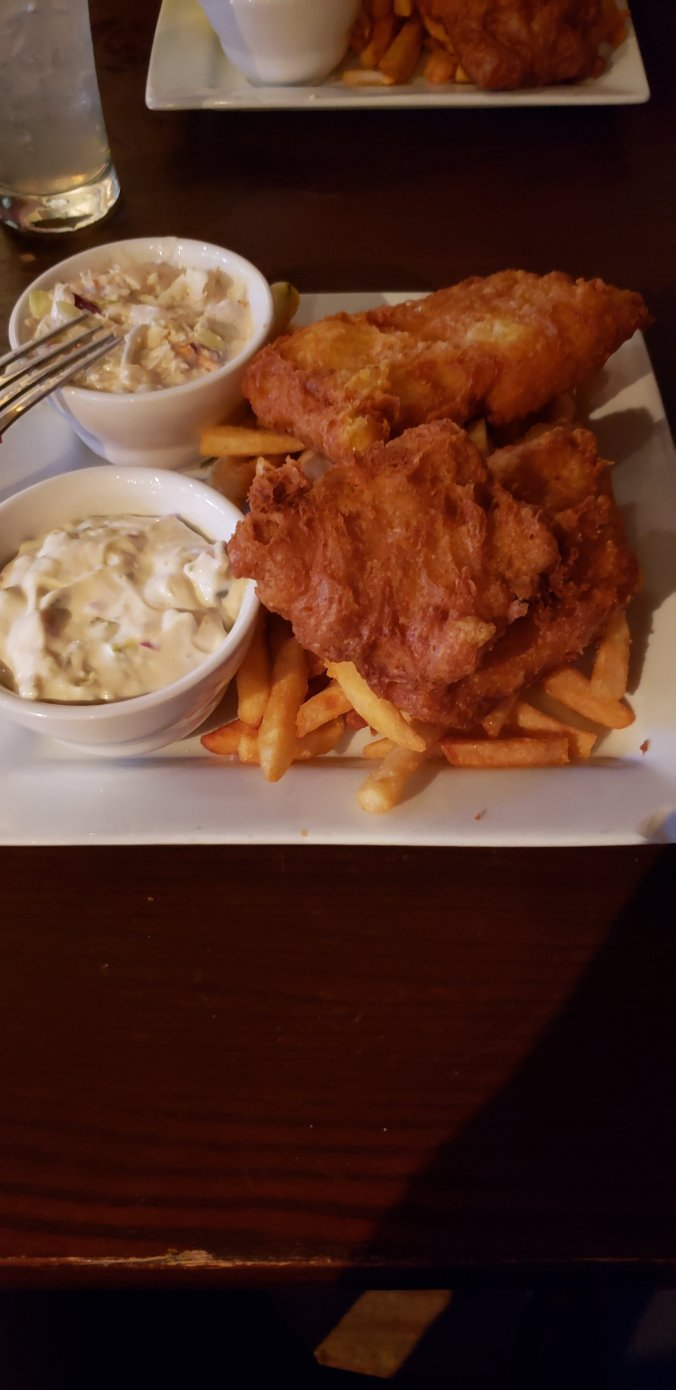 A plate of fish and chips with two fried pieces of cod on top of a pile of french fries